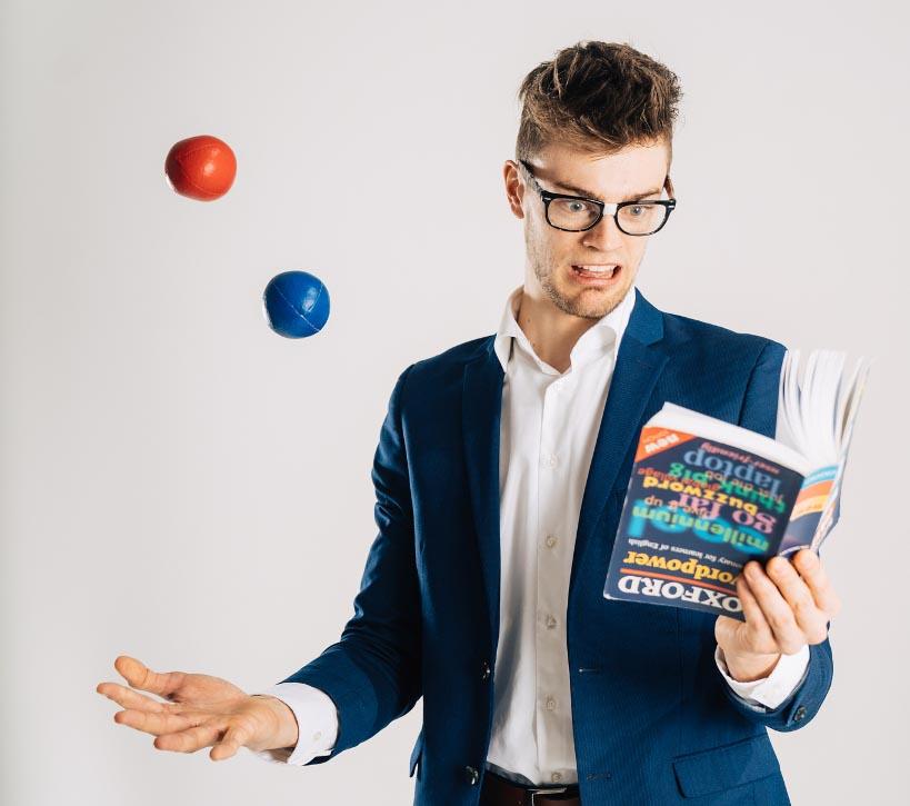 Jongleur Bart Hoving jongliert 2 Bälle während er ein Wörterbuch falsch herum versucht zu lesen